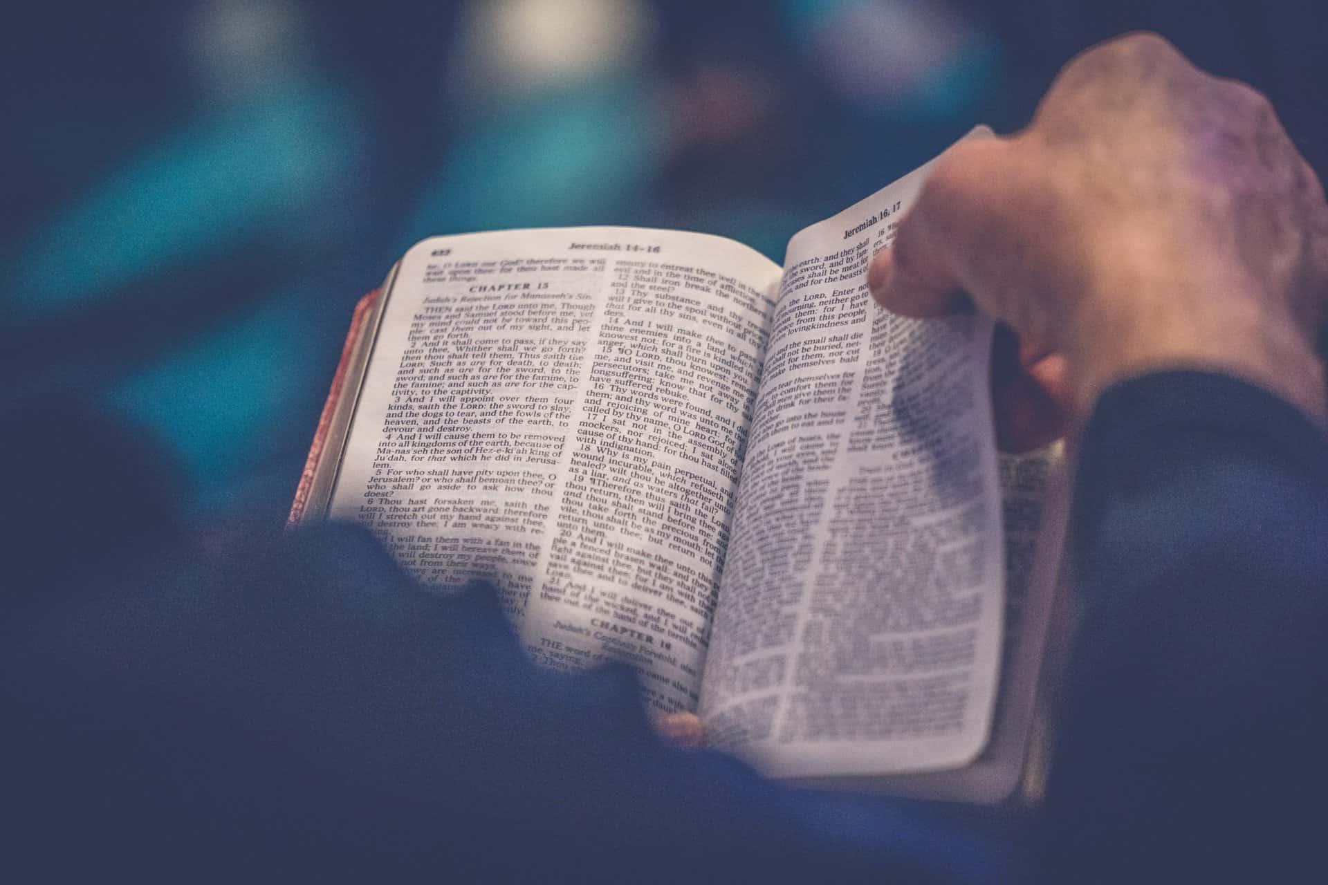 Selän takaa otettu kuva, kun ihminen selailee Raamattua