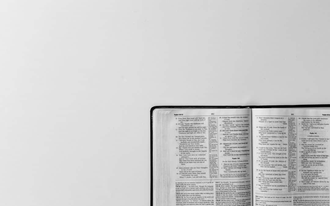 Valkoinen tausta, oikeassa alakulmassa näkyy osa avatusta Raamatusta